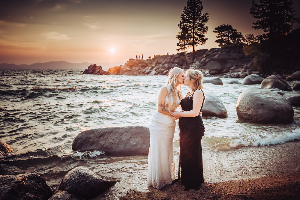 A lgbqt couple kissing on a rock at Secret Cove during their California Elopement