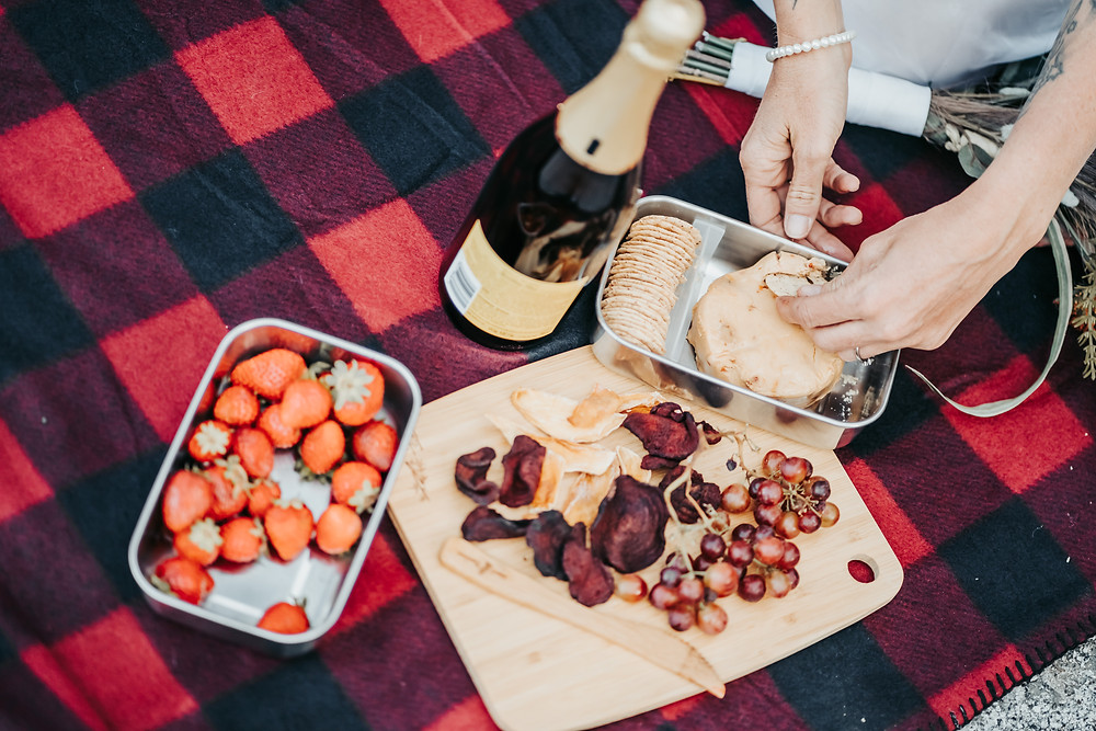Picture of a picnic with strawberries, wine, cheese and crackers, grapes and dried fruit.  Photos showing eloping in Lake Tahoe