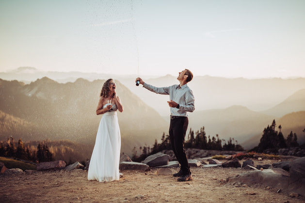 Champagne toast with a bride and groom on top of a mountain with the sunset and mountains in the background