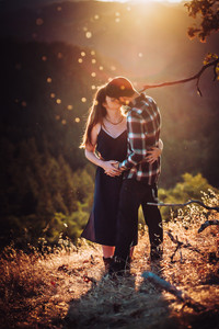 A couple kissing under a mountain sunset during their mini moon