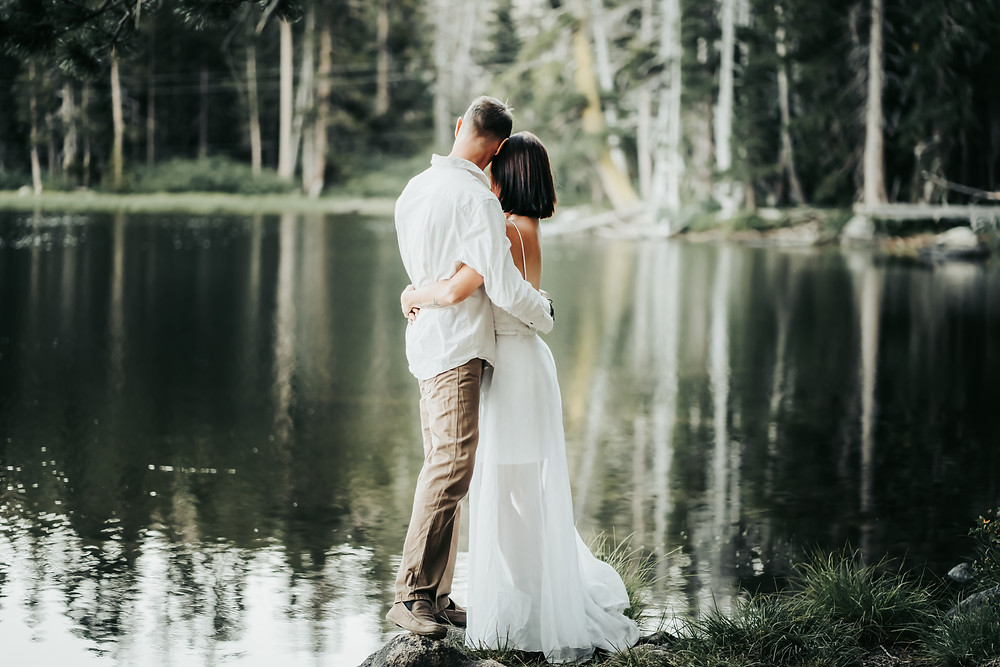 Bride and Groom embracing an looking out on a reflecting lake in Lake Tahoe.  Photo is Eloping in Lake Tahoe