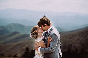 A bride and groom kissing and holding each other overlooking california mountains