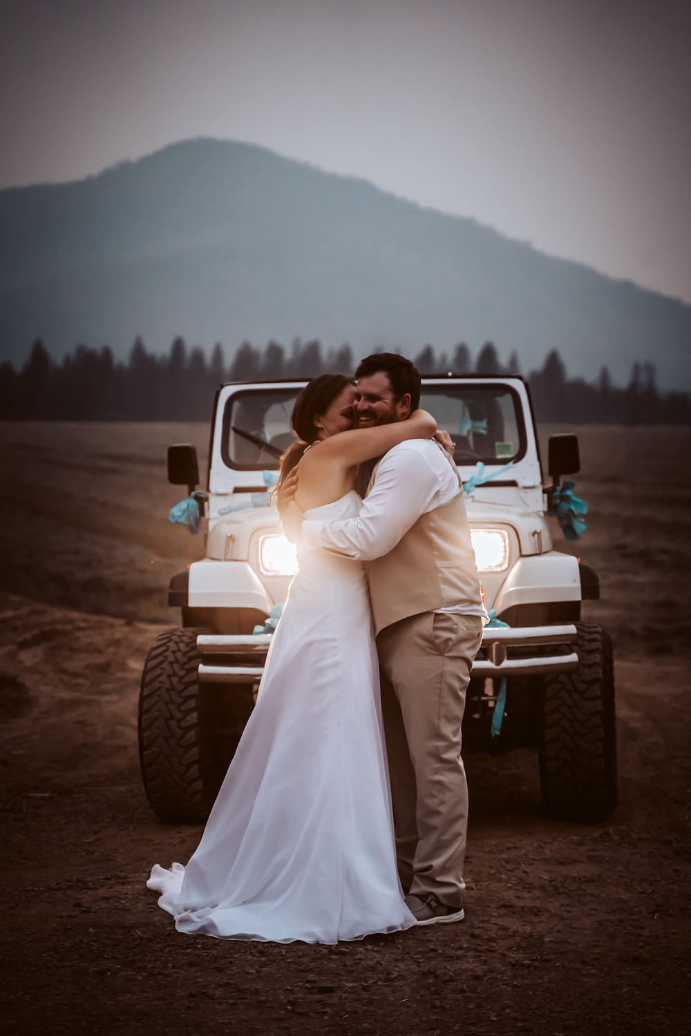 Bride and groom hugging in front of a jeep with lights on and mountains in the background