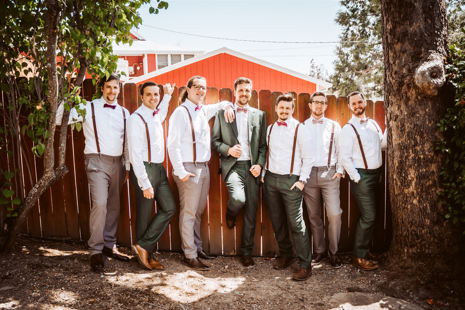 Groomsmen all leaning against a fence for their wedding day portrait
