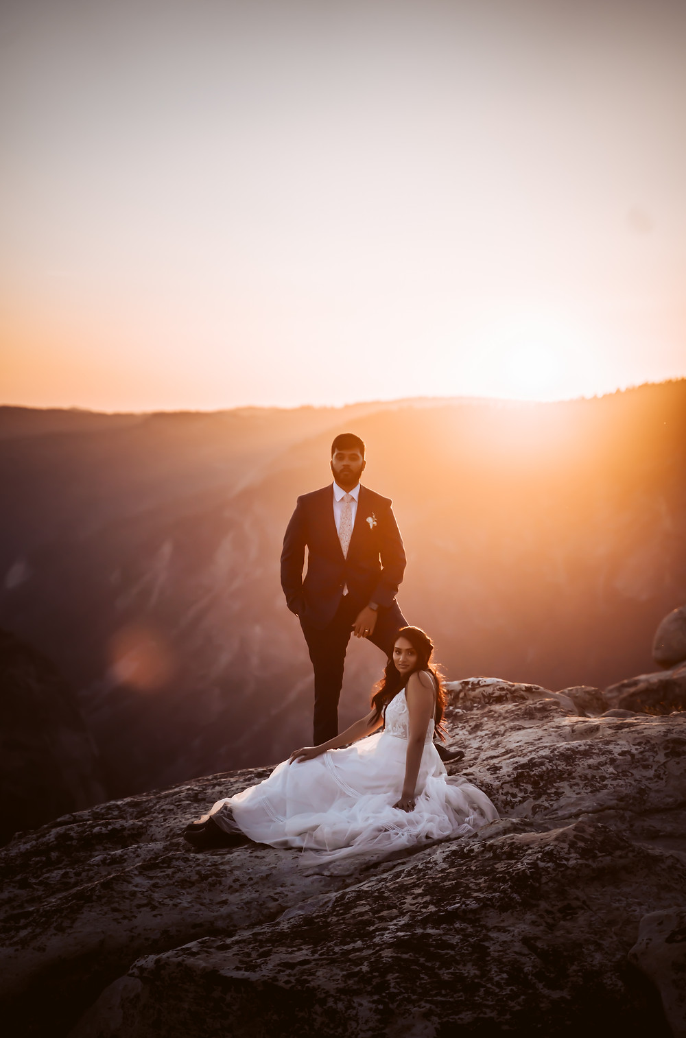 A wedding elopement couple sitting on a rock in front of a sunset overlooking the Yosemite Valley