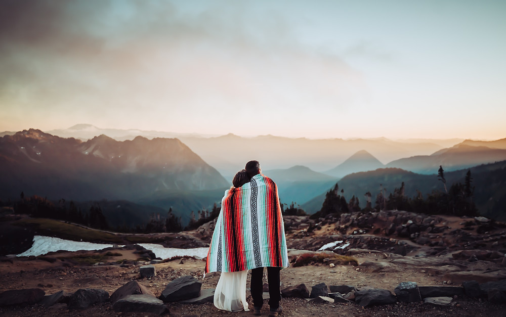 A couple wrapped in a mountain blanket looking out into the sunset on the mountains at Mount Rainier
