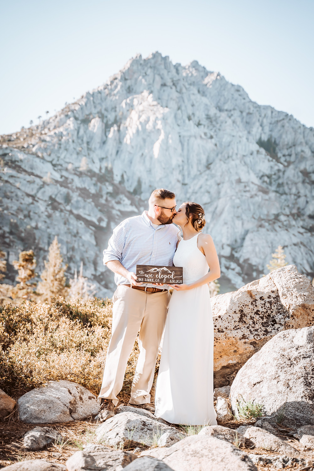 A wedding couple kissing in front of a mountain backdrop holding a sign that says We Eloped in Lake Tahoe