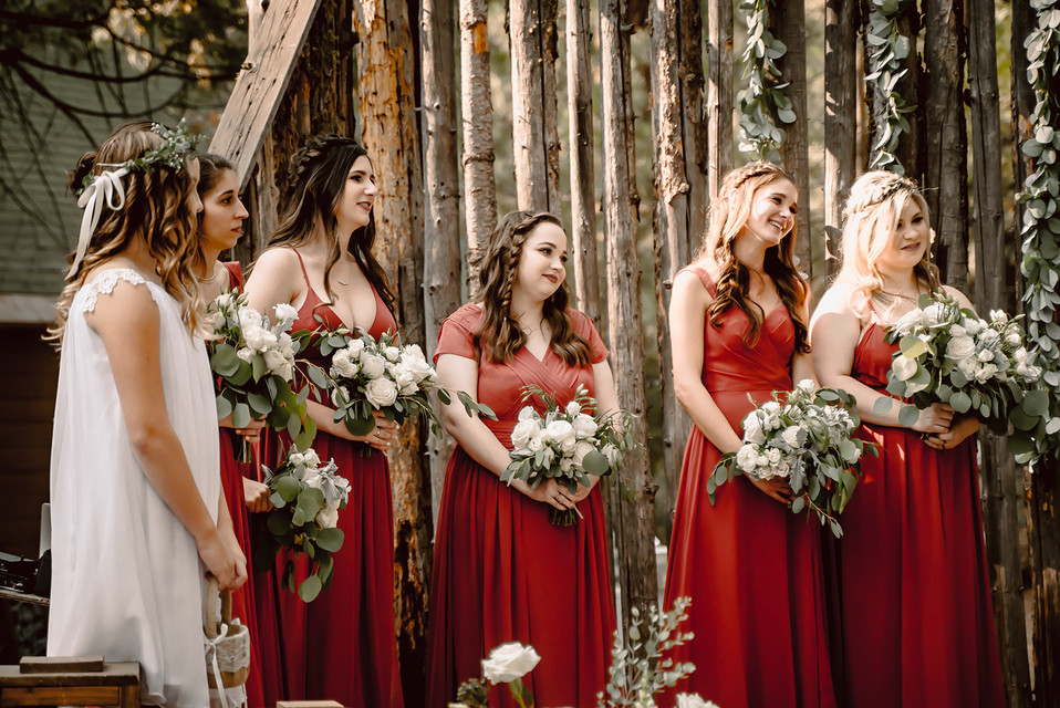 The Bridal party standing at the ceremony wearing red dresses for an outdoor wedding at Camp Sylvester in Pinecrest California