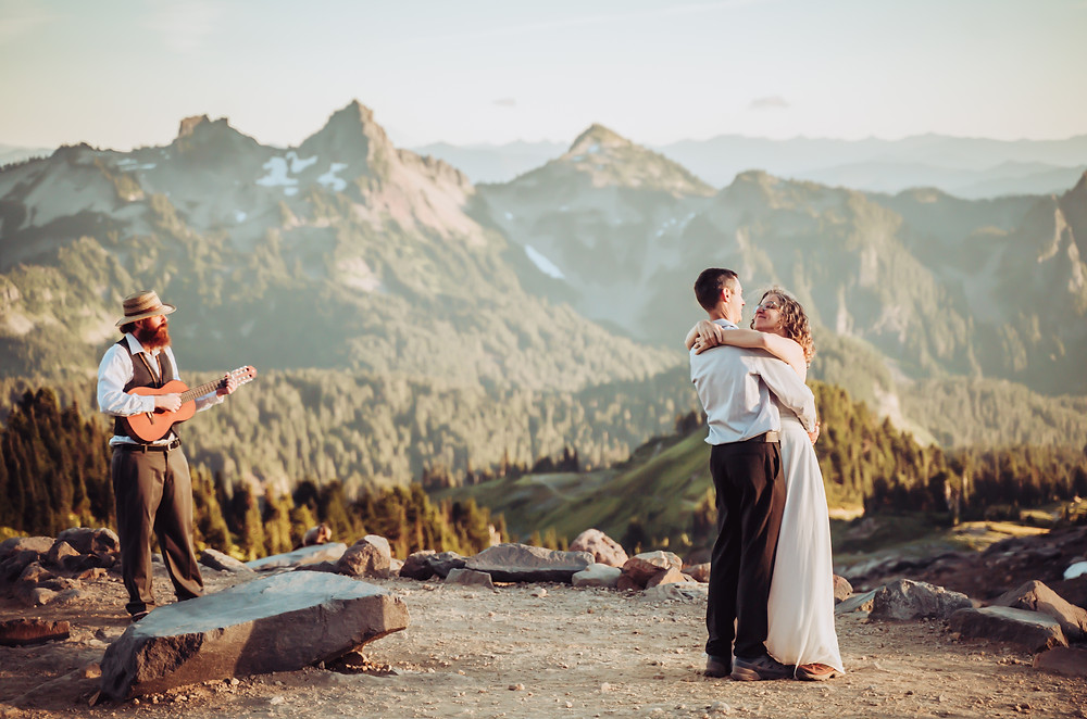 Bride and Groom dancing for their first dance on their Mt. Rainier Elopement with a live musician with a guitar and Mountains in the background