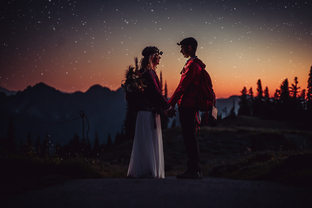 Bride and Groom holding hands looking at each other wearing headlamps and the sky is full of stars