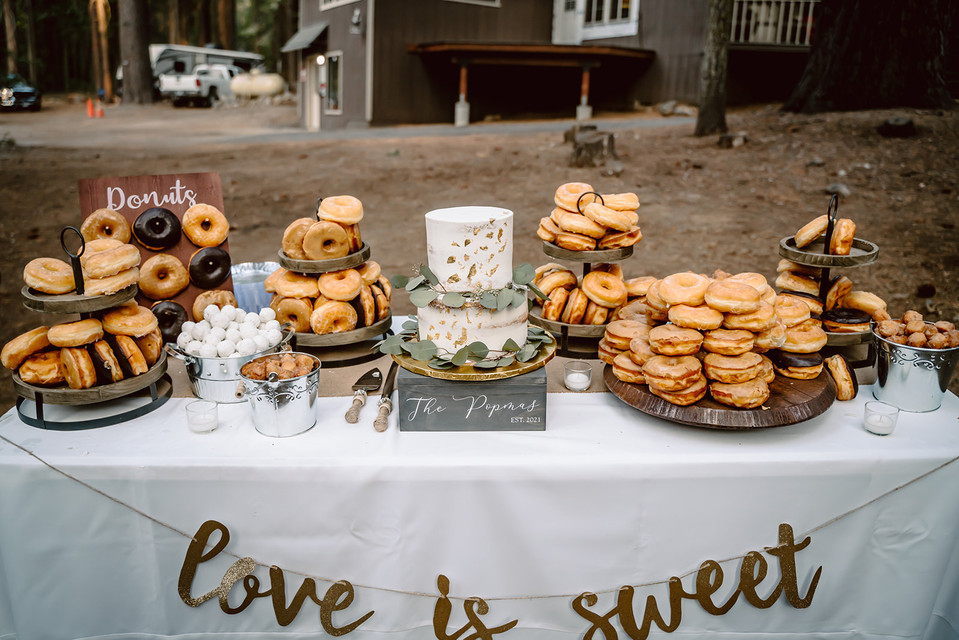 A desert table with a wedding cake and donuts for an outdoor wedding reception in California