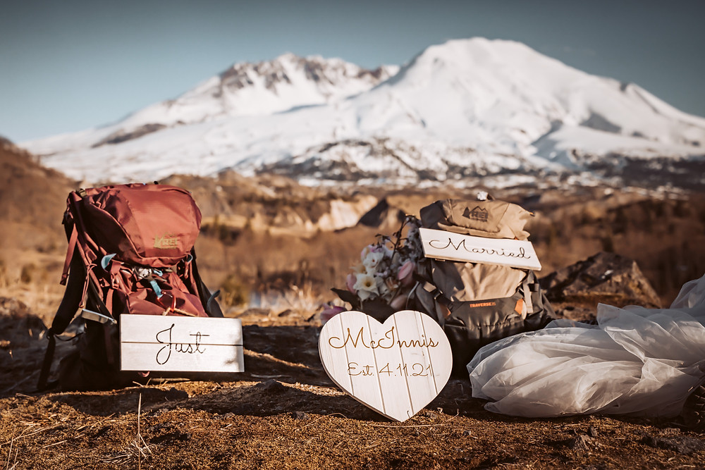 A bride and grooms backpacks laying on the ground with their Just Married signs and personalized wedding sige with their date on it in front of Mt. St. Helens for their elopement