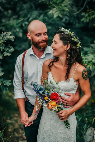 A bride and groom holding each other in the forest wearing a flower crown and brown suspenders