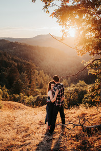 A couple hugging with the mountain sunset backdrop during their mini moon photos shoot in Northern California