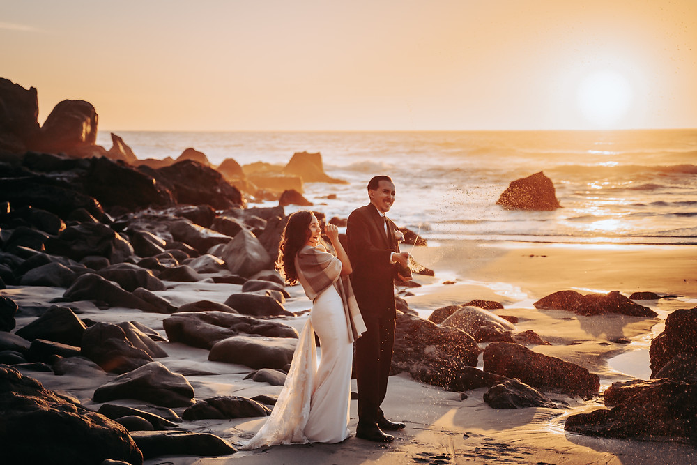 A bride and groom popping the champagne during sunset on their elopement day for the end of their elopement timeline