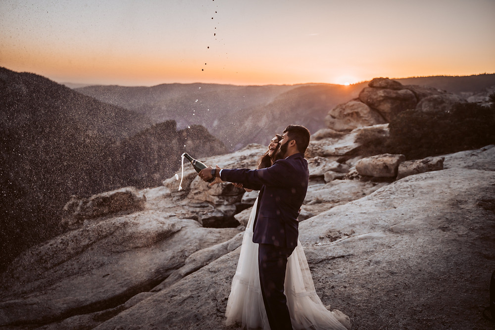A wedding couple popping a bottle of champagne at sunset in Yosemite at Taft Point for their California Elopement