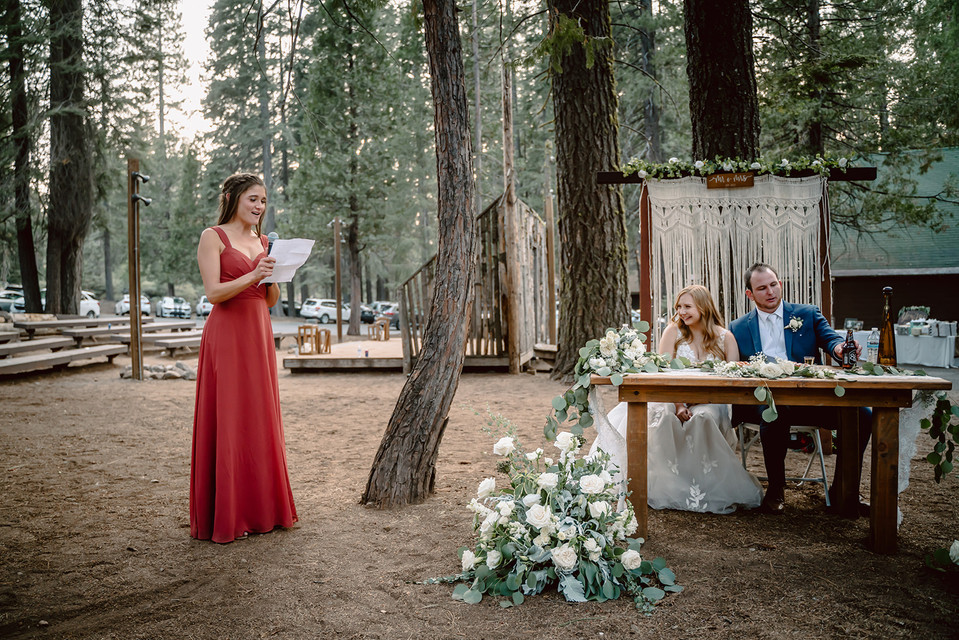 A bridesmaid giving her maid of honor speech to the recently married couple at Camp Sylvester in Pinecrest, California