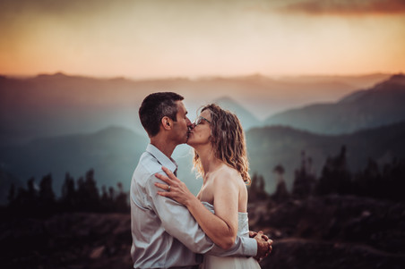 Bride and groom kissing in front of a mountain sunset
