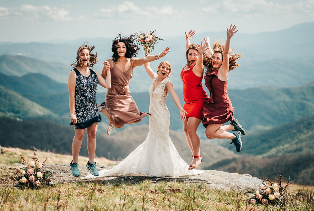 A bride jumping with her bridesmaids in front of the blue ridge mountains after her elopement ceremony