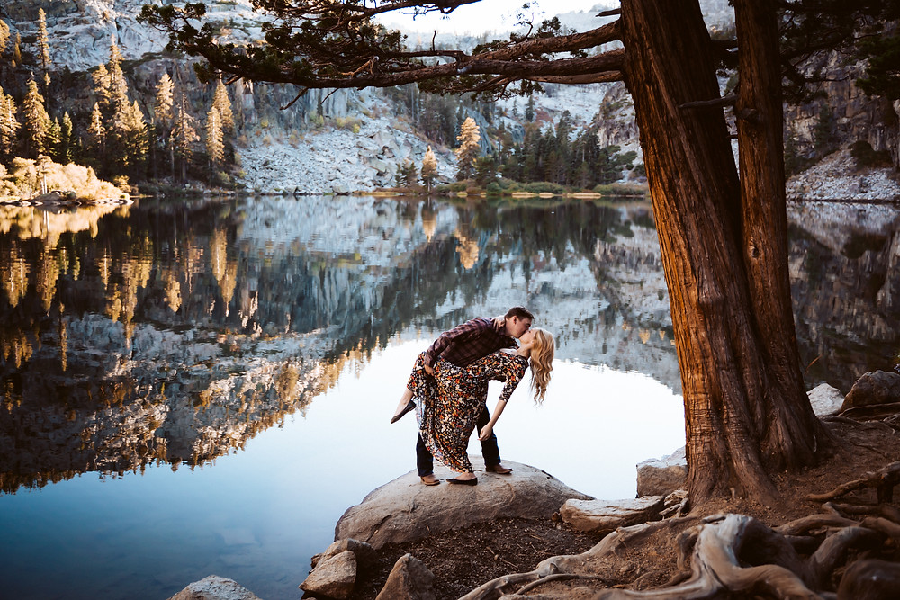 A couple doing a dip pose in front of a lake reflection and standing on a rock in Lake Tahoe