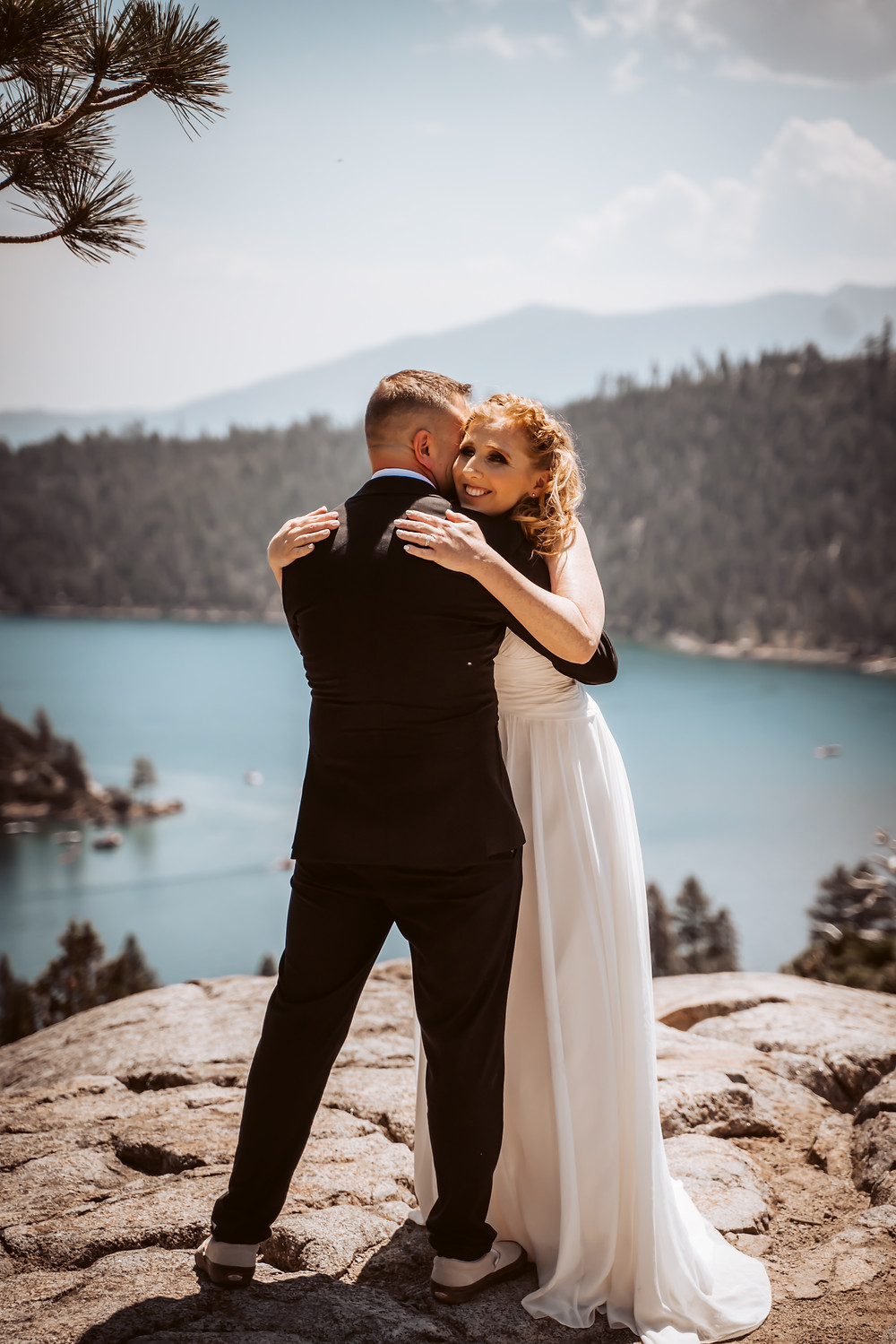 A wedding couple hugging standing on a rock overlooking Emerald Bay in Lake Tahoe for their Lake Tahoe Elopement
