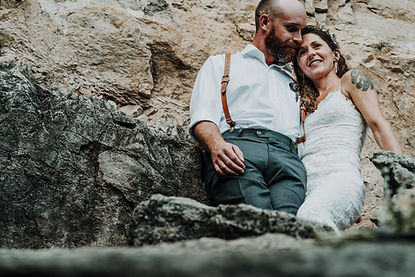 A wedding couple standing on some boulders and looking out onto the landscape