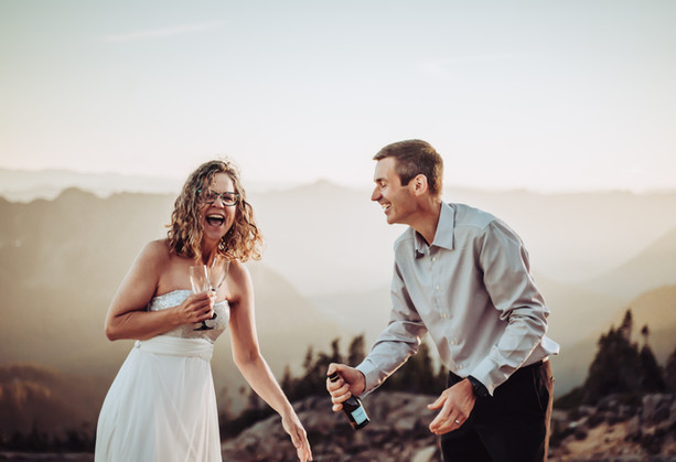 Bride and Groom Laughing after their champagne toast on top of the mountain for their Mt. Rainier Elopement
