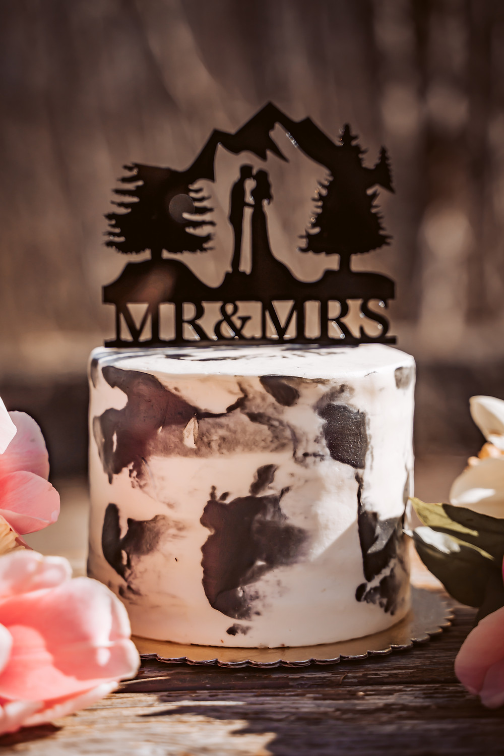 A mountain wedding cake with a topper that says Mr. and Mrs with a bride and groom kissing with a mountain backdrop