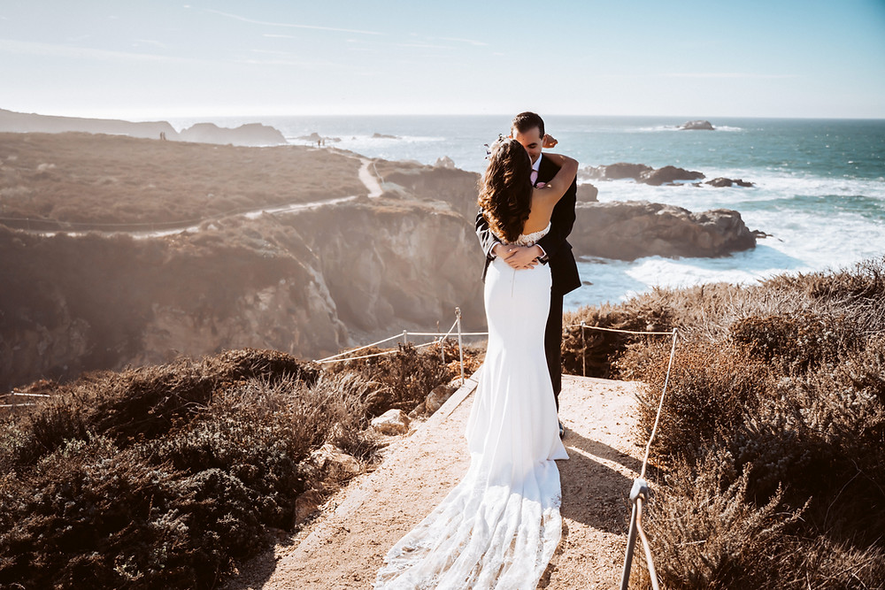 A wedding couple hugging and looking out onto the cliffs of Big Sur for their first look on their elopement day