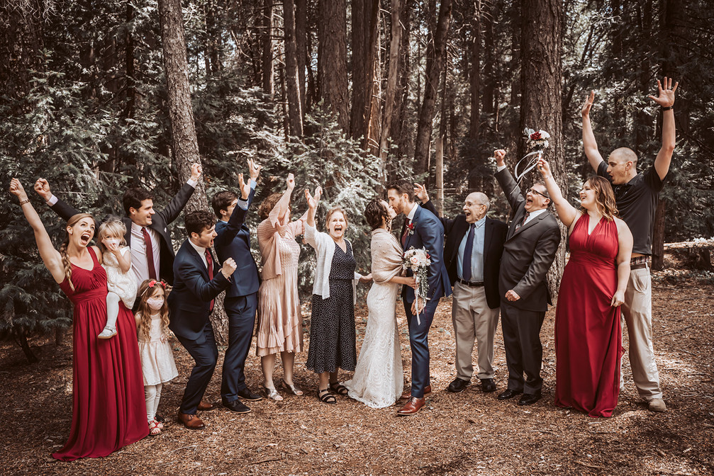 A family portrait with the bride and groom kissing and family cheering in front of the forest trees at the Harmony Ridge Lodge in Nevada City for their wedding day