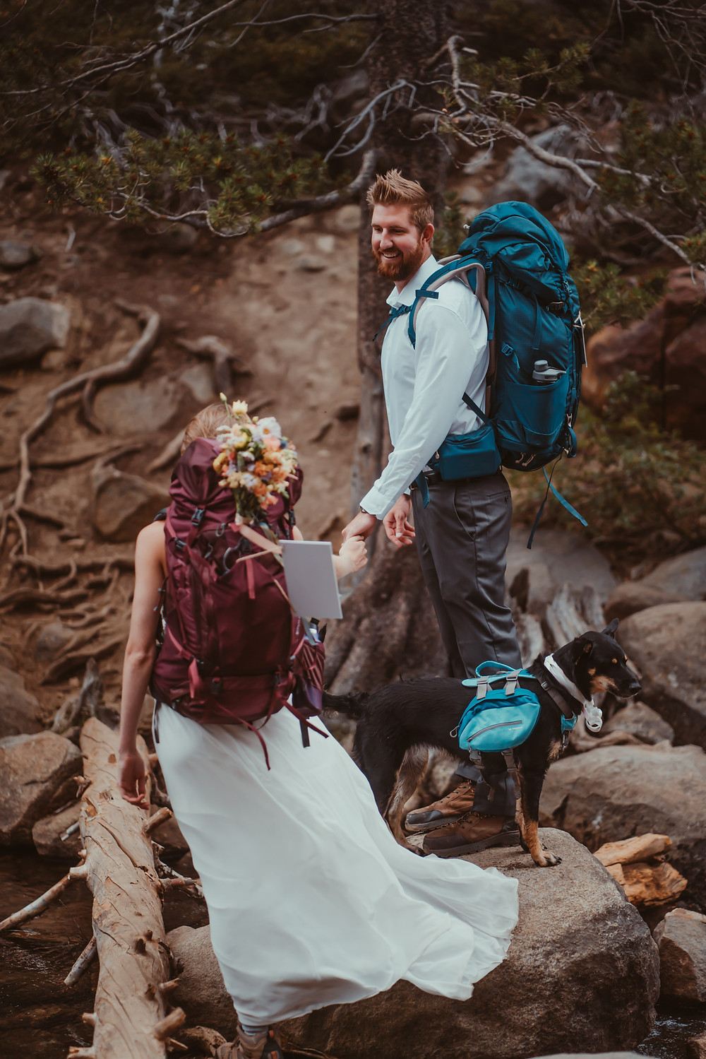 Bride and Groom crossing a stream with their hiking backpacks on for an hiking elopement in Lake Tahoe