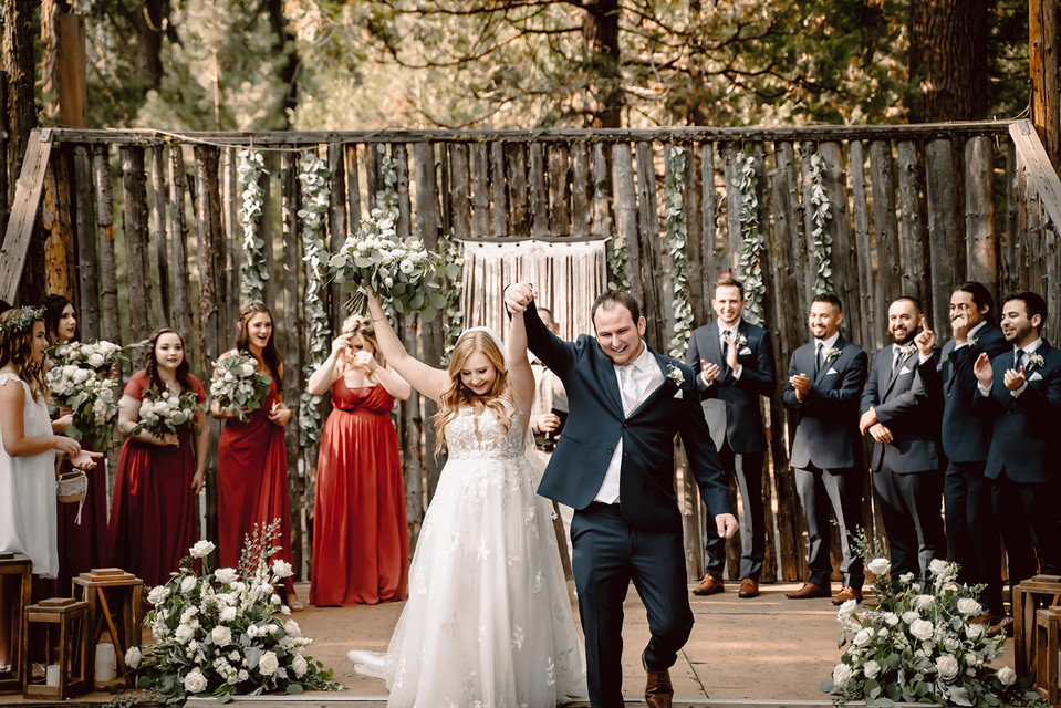 A bride and groom with their hands in the air after they have been introduced as married for the first time at their forest wedding