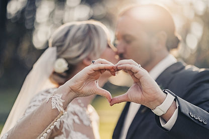 A bride and groom making a heart with their hands and kissing in the background with the sun shining on their head