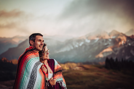Bride and groom with a mountain blanket over their shoulders looking at the mountain sunset