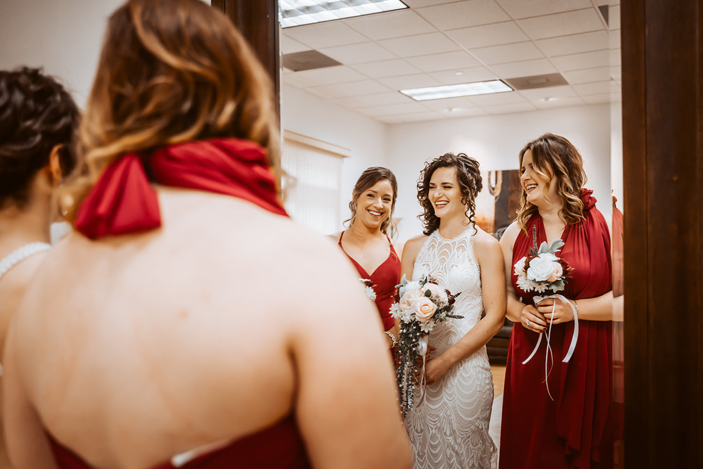 A bride and her bridesmaids smiling in the mirror and getting ready for their wedding day