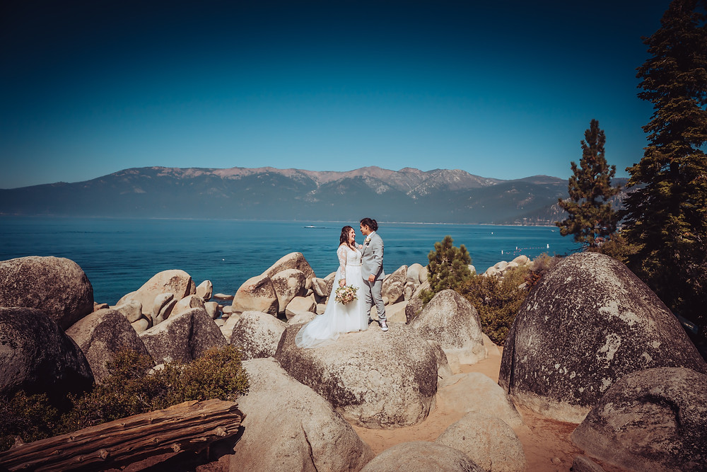 A bride and groom standing on a giant boulder over looking Lake Tahoe during their elopement