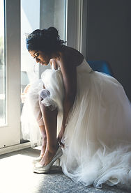 A bride standing by the window and putting her shoes on