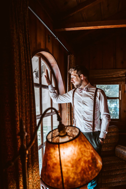 A groom wearing suspenders looking out his window getting ready for the wedding day