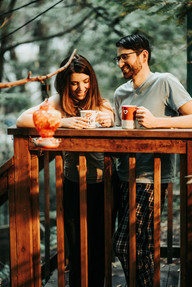 A couple drinking coffee outside their cabin in the woods in Northern California during their mini moon