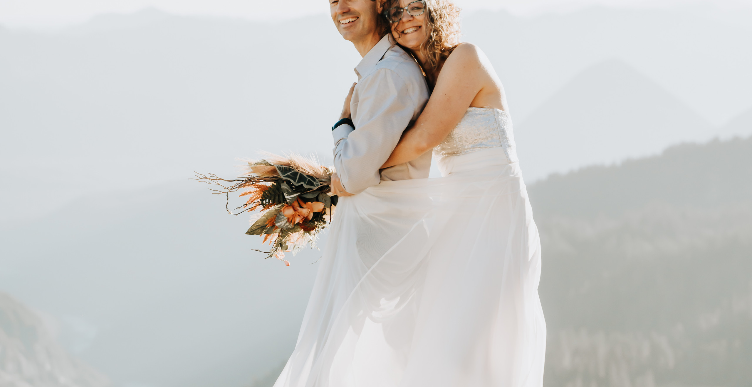 Bride holding the groom from behind and smiling with a sunset and a mountain backdrop at Mt. Rainier