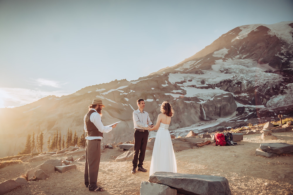 A couple standing in front of an officiant with Mount Rainier in the background