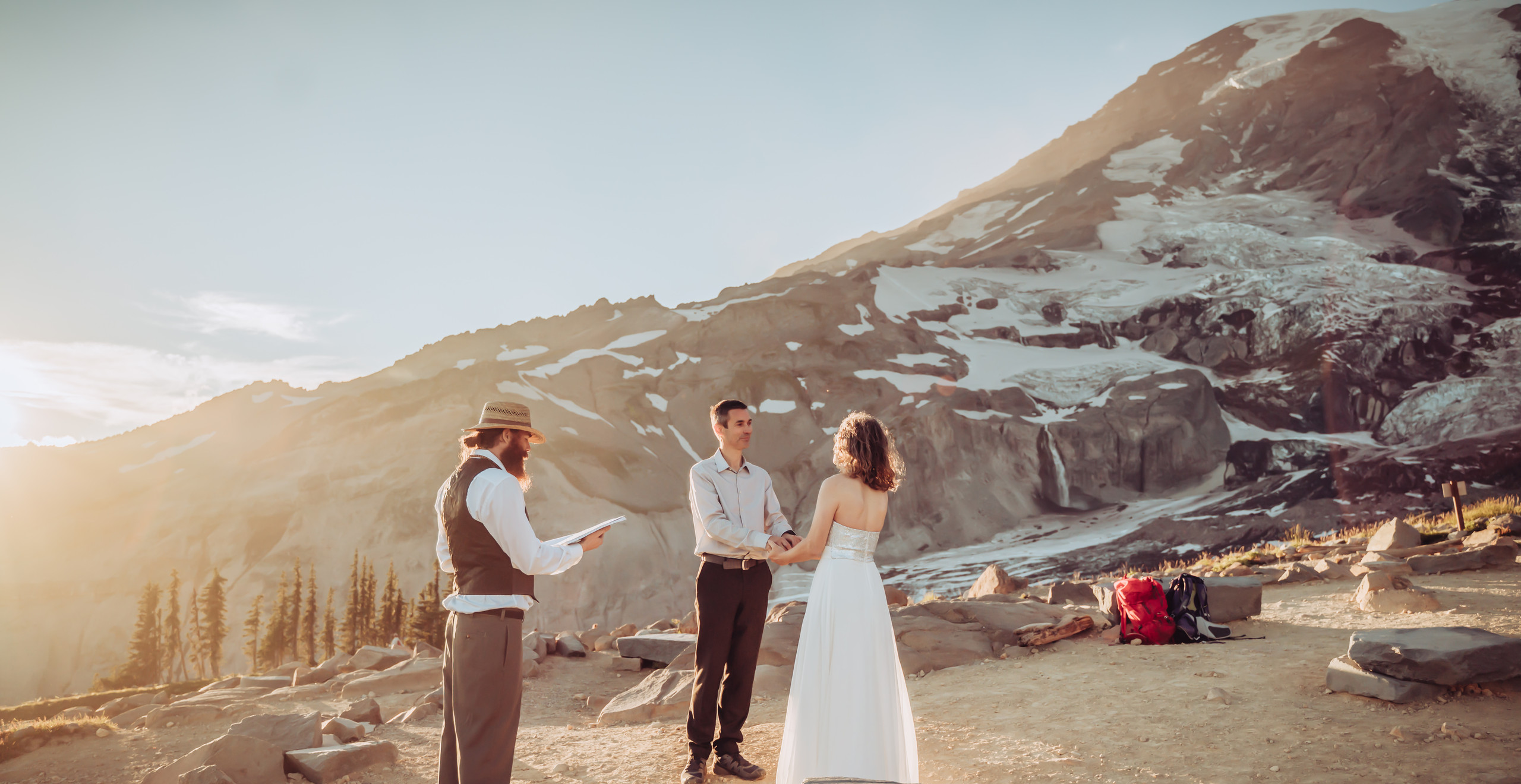 Officiant doing the vow ceremony for the Mt. Rainier Elopement with Mt. Rainier in the background