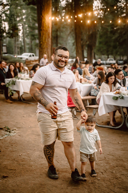 A father holding hands with his toddler walking through the wedding reception in the forest