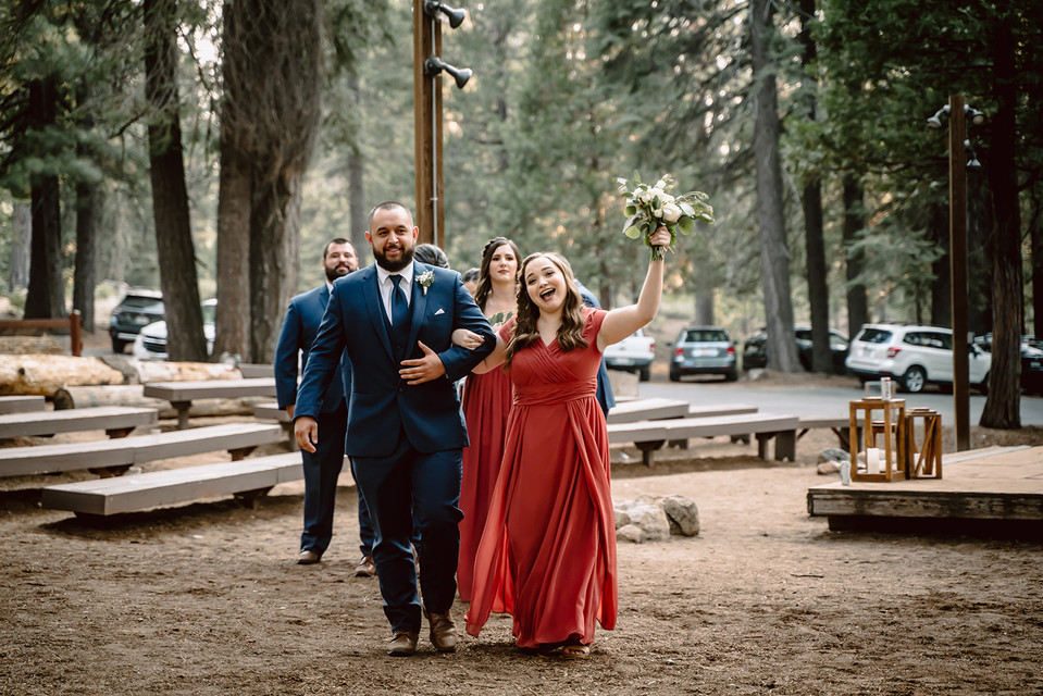 A bridesmaid getting introduced for the grand entrance at an outdoor reception at Camp Sylvester in Pinecrest California for a wedding day