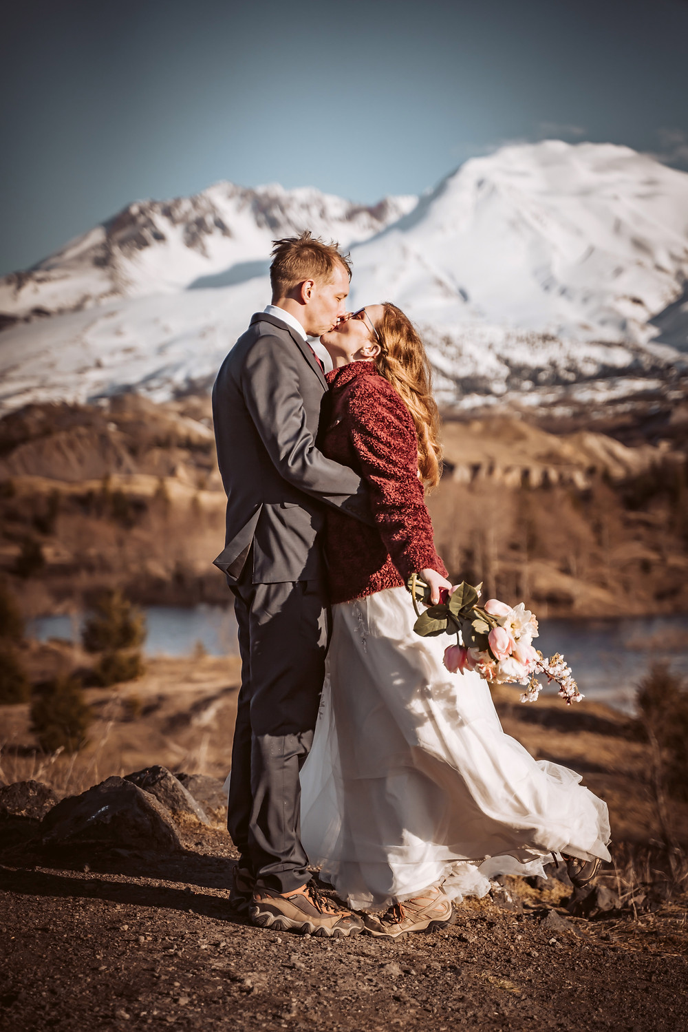 A couple in their wedding attire kissing in front of Mount St. Helens on their elopement day for their couples portion of the photos on their elopement timeline