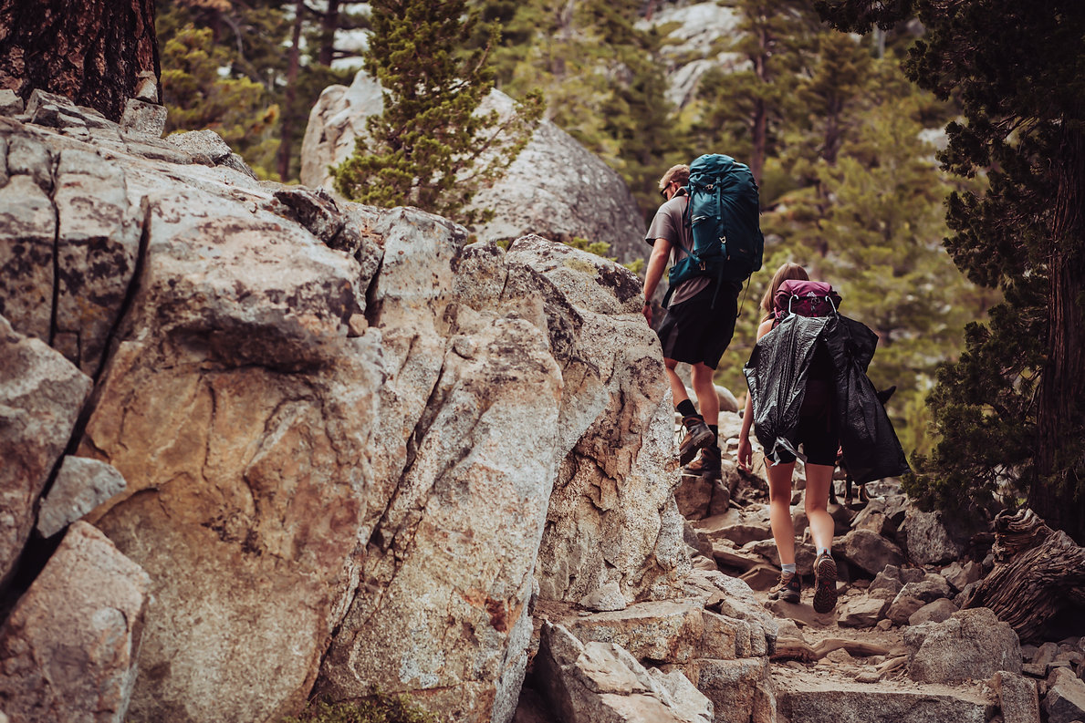 A wedding couple hiking their wedding clothes up the mountain in Lake Tahoe for their wedding elopement