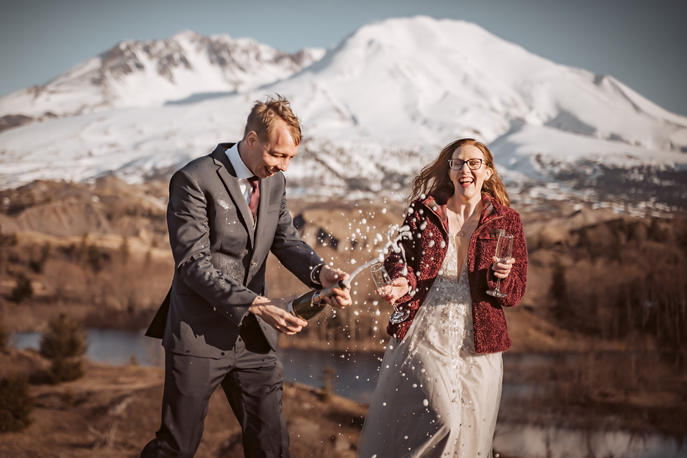 A bride and groom popping their champagne for a toast in front of Mt. St. Helens for their elopement