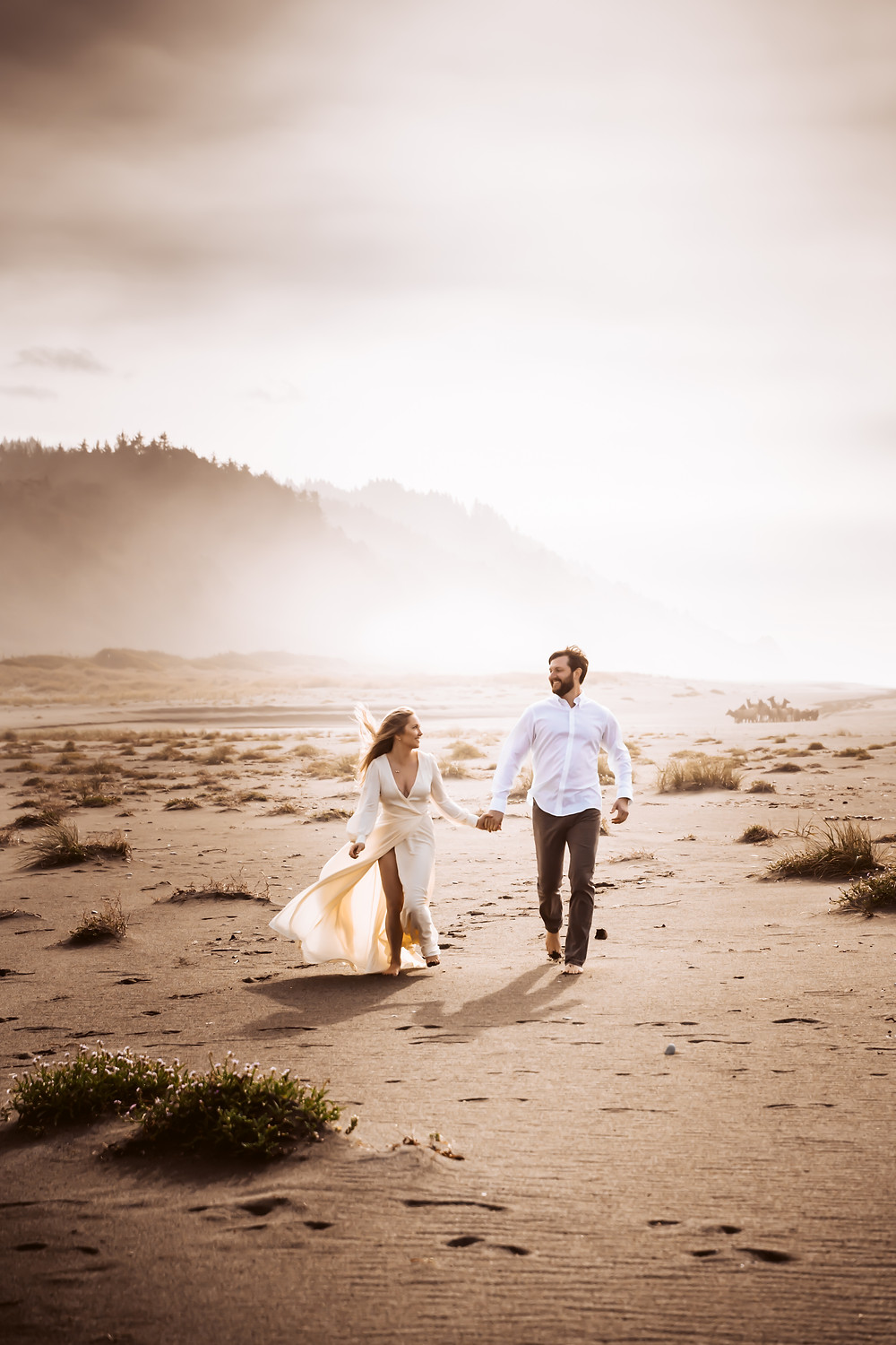 A wedding couple running on the foggy beach with mountain in the backdrop during their California Elopement