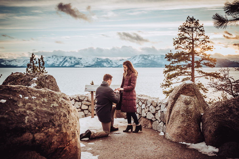 A guy down on one knee proposing to his girlfriend in front of a sunset in Lake Tahoe in the winter