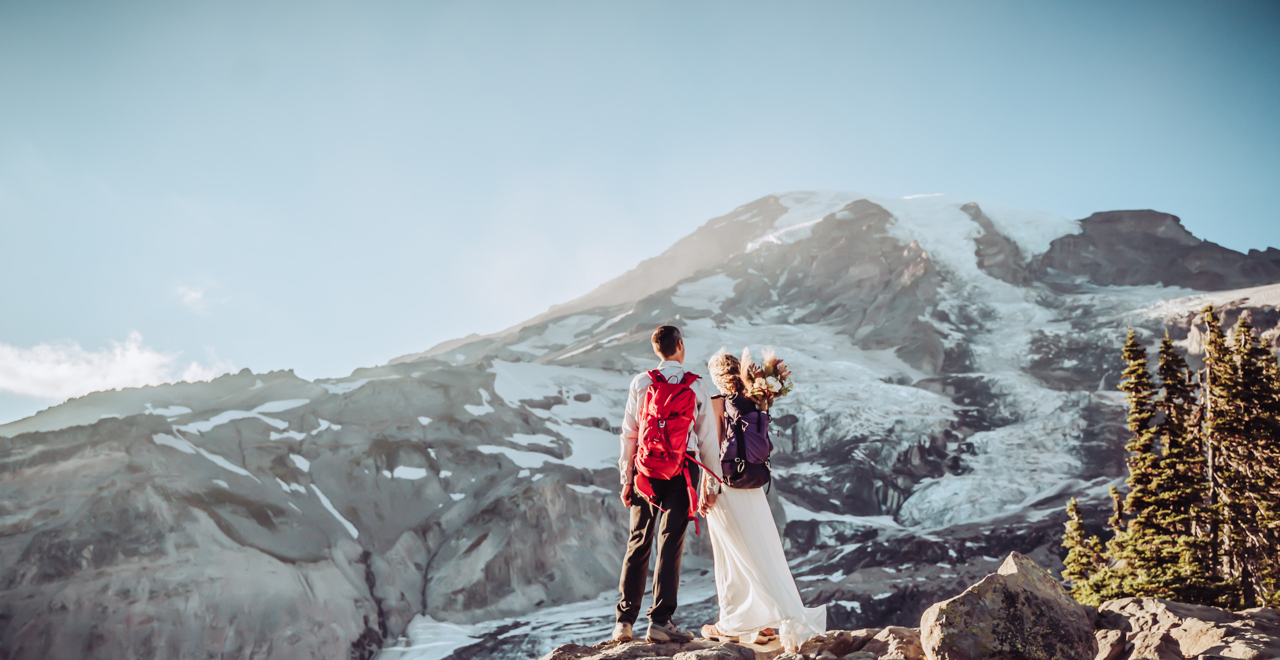 Bride and groom dressed up in wedding attire wearing hiking backpacks, standing on a rock facing the snow covered Mt. Rainier